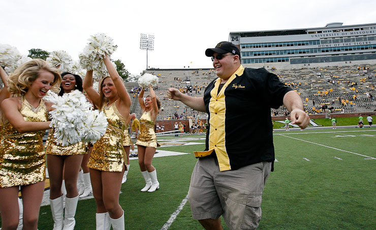 "David Champlin of the ""Big Mo"" drum crew, who lead the MIZ-ZOU cheers at football games, celebrates the Missouri Tigers' victory over the Furman Paladins with the Golden Girls at the end zone of Faurot Field on Saturday, September 19, 2009 in Columbia, Mo.  The Tigers defeated the Paladins 52-12."