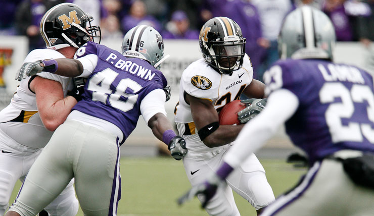 Tim Barnes, left, Missouri's offensive lineman, holds back Kansas State's defensive end Prizell Brown to make a path for Missouri's ball carrier, tailback Derrick Washington, during the first quarter of the game on Saturday, Nov. 14, 2009 in Manhattan, Kan.  The Tigers defeated the Wildcats 38-12.