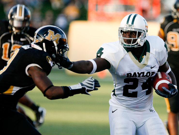 Baylor Bears' running back Terrance Ganaway stiff-arms Missouri Tigers' safety Jasper Simmons in the fourth quarter.