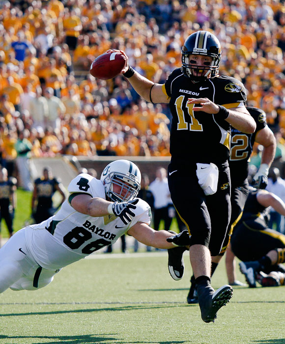 Missouri Tigers' quarterback Blaine Gabbert attempts a pass while the Baylor Bears' Jason Lamb dives after him during the second quarter of the game.