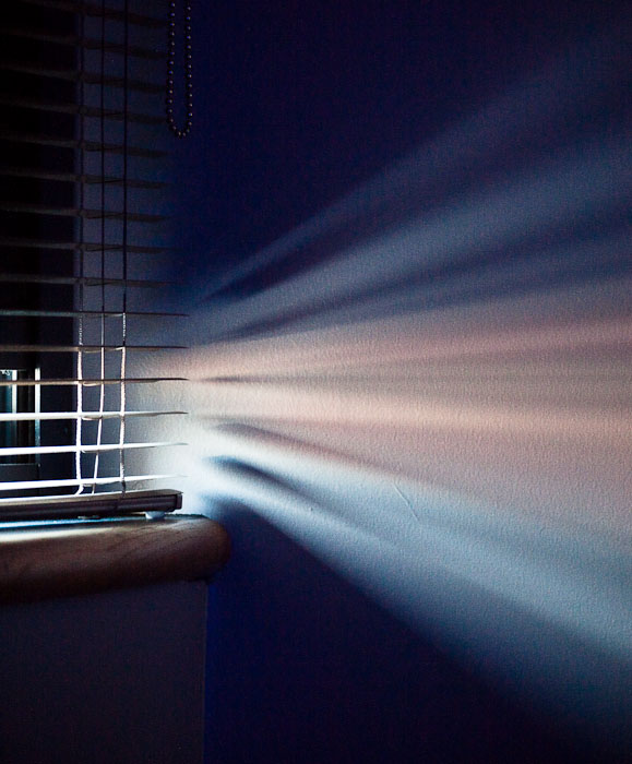Light streams through the blinds as if through a prism