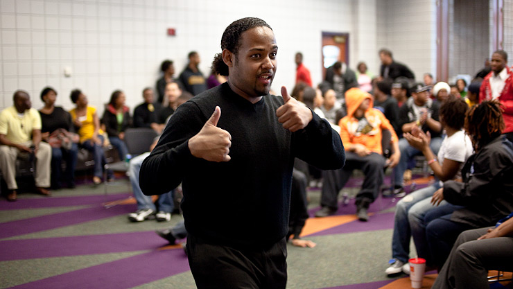 "Jarrad Henderson gives a ""thumbs-up"" at the reception for prints from his master's project, ""Beyond This Place,"" at the Black Culture Center at the University of Missouri."