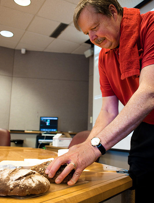 David Rees sclices the bread before class