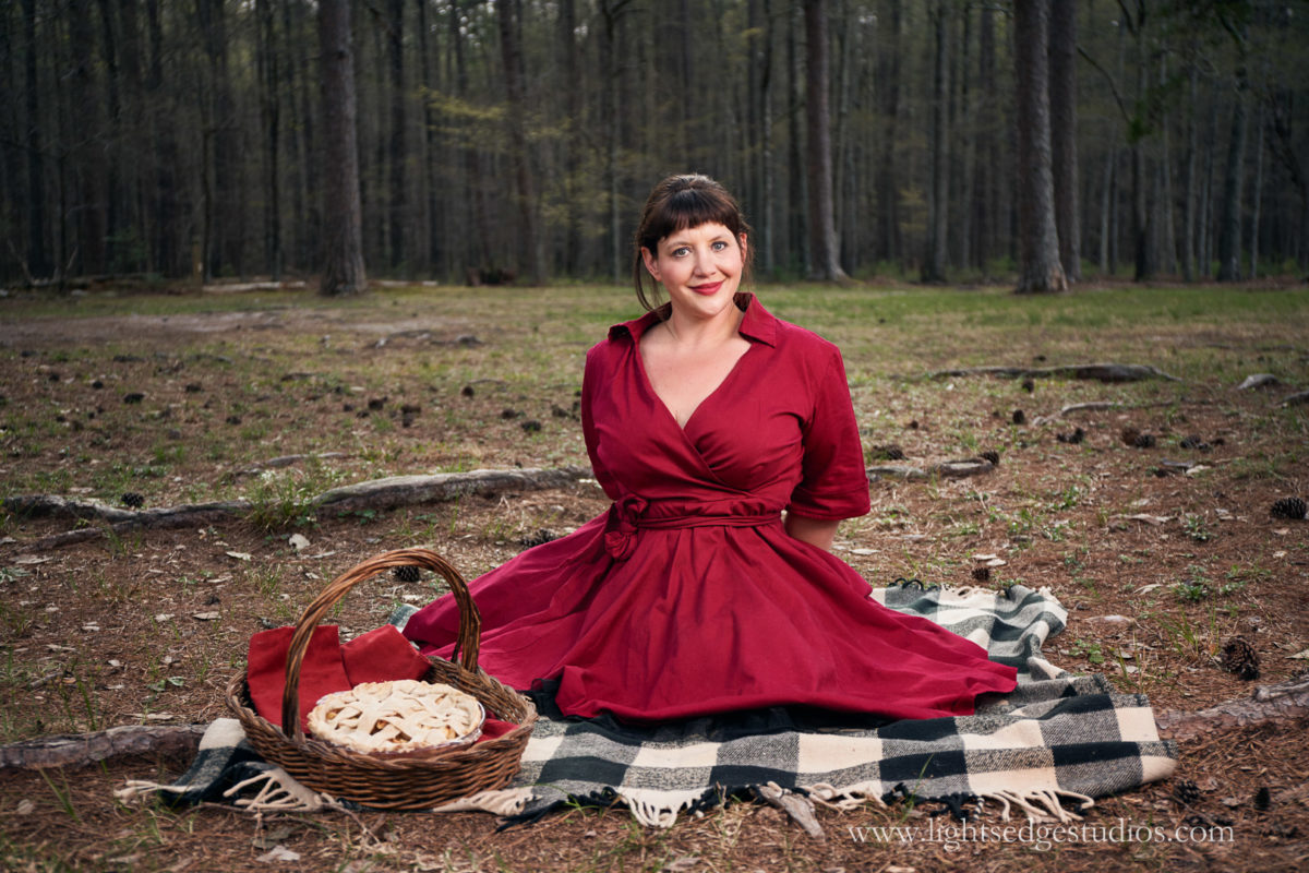 A woman wearing a red dress kneels in a park next to a wicker basket and a homemade pie. Photographed with a Sony A7R III and Canon 24-70 f/4L IS lens adapted with the Sigma MC-11